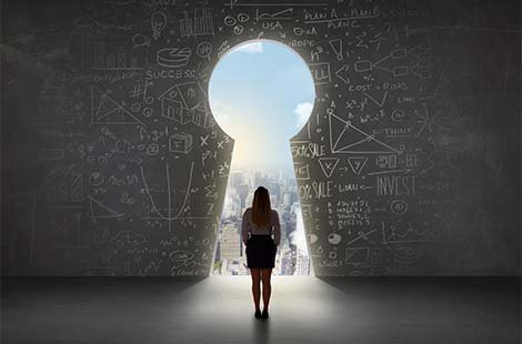 Business woman looking at keyhole with bright cityscape concept background - New Horizons Program